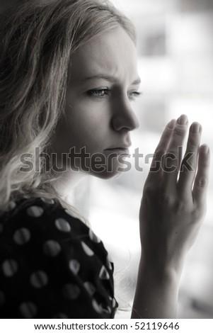 Sad woman looking at window - stock photo