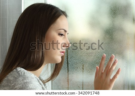 Sad woman looking the rain falling through a window at home or hotel - stock photo