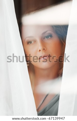 Sad woman looking through a window. - stock photo