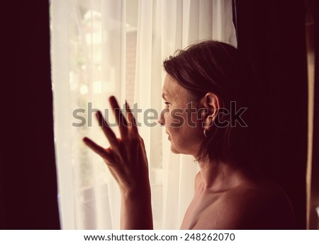 Sad woman looking through a window.  LOMO effect - stock photo