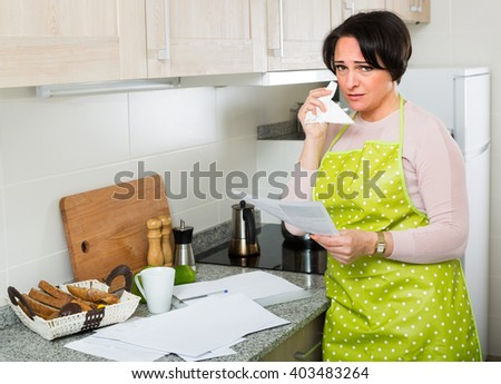 Sad woman looking through financial documents and crying at home kitchen