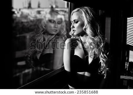 sad woman looking through the window.  - stock photo