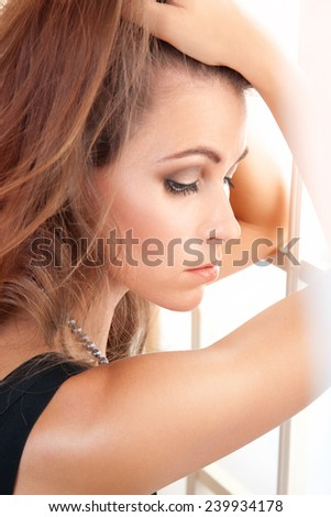 sad woman looking through the window - stock photo