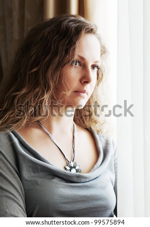 Sad woman looking through the window - stock photo