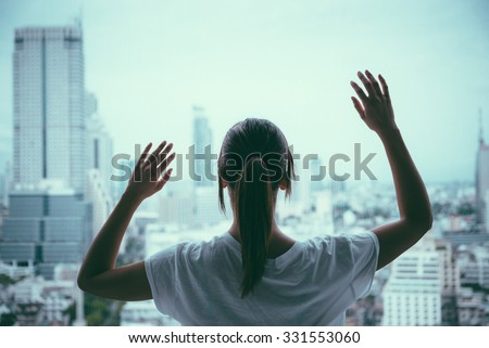 Sad woman looking through the window at grey rainy city looking depressed. Depression, problems and loneliness concept. - stock photo