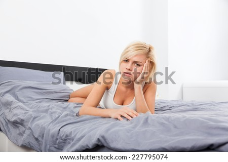 sad woman lying on bed home, young blond girl unhappy white underwear modern bedroom - stock photo