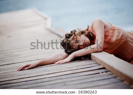 Sad woman lying on berth over sea background - stock photo