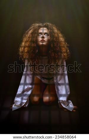 sad woman prisoner looking up in dark prison - stock photo