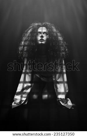 sad woman prisoner looking up in dark prison. monochrome image - stock photo