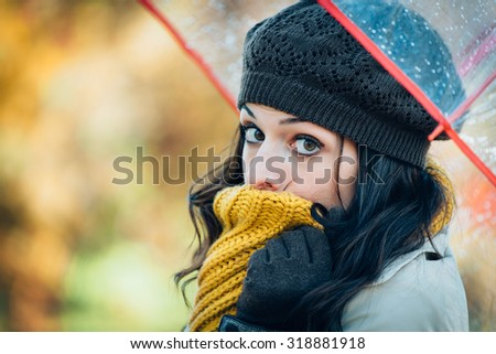 Sad woman shivering and suffering cold autumn wind and rain. Brunette female covering her mouth with warm scarf because of fall season bad weather. - stock photo