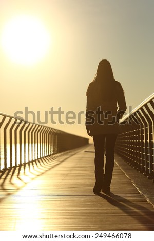 Sad woman silhouette walking alone on a bridge on the beach in winter at sunset - stock photo
