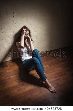 Sad woman sitting alone in a empty room - stock photo