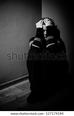 sad woman sitting alone in a empty room - black and white - stock photo
