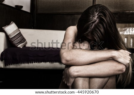 Sad woman sitting alone in a empty room next to the bed. domestic violence - stock photo
