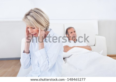 Sad Woman Sitting At The Edge Of Bed In Front Of Man
