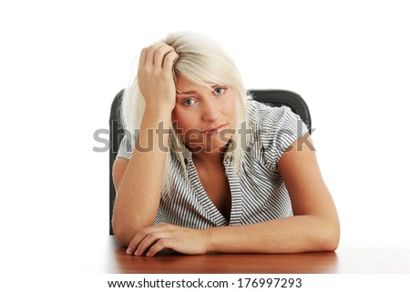 Sad woman sitting behind the desk