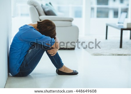 Sad woman sitting by wall at home
