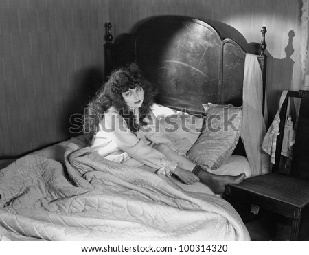 Sad woman sitting in bed - stock photo