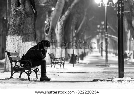 Sad woman sitting on a bench in winter time. - stock photo