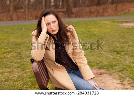 Sad woman sitting on a bench on a cloudy day with a coat looking lonely
