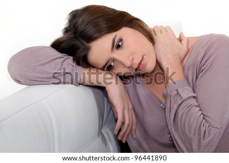 Sad woman sitting on a sofa - stock photo