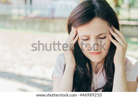 Sad woman sitting on bench outdoors . Pain