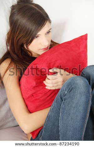 Sad woman sitting on couch and squeezing pillow. - stock photo