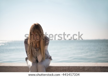 Sad woman sitting on stone wall with sea in the background, crying and covering her face. - stock photo