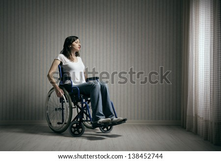 Sad woman sitting on wheelchair in empty room