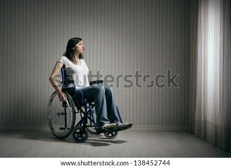 Sad woman sitting on wheelchair in empty room - stock photo