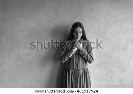 Sad woman standing beside the grunge wall