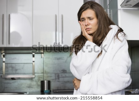 Sad woman suffering from toothache standing in kitchen - stock photo