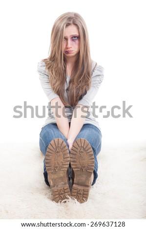 Sad woman victim of domestic violence sitting injured on the floor - stock photo