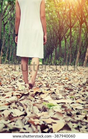 Sad woman walking alone in the forest feeling sad and lonely - stock photo