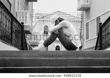 sad woman wearing a hat and hugging knees on stair, back and white