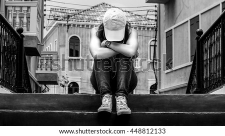 sad woman wearing a hat and hugging knees on stair, backand white