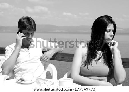 Sad woman while boyfriend talking on the phone  - stock photo