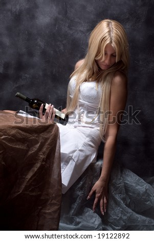 sad woman with bottle of wine, studio dark - stock photo