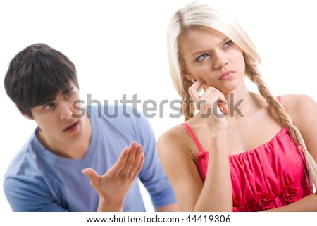 Sad woman with pensive expression touching her face on background of displeased man