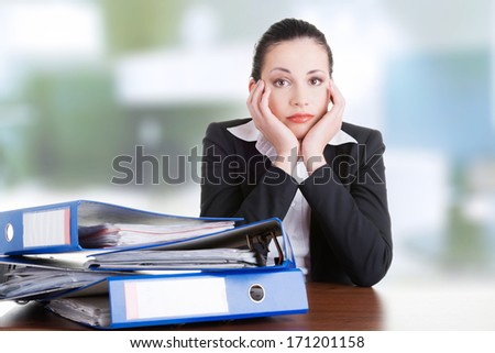 Sad woman with ringbinders sitting at the desk. Tired and exhousted business woman.  - stock photo