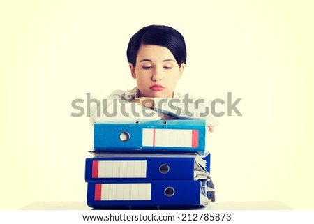 Sad woman with ringbinders sitting at the desk. Tired and exhousted business woman.