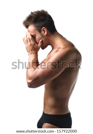Sad, worried or unhappy young muscular man with hands on his head, isolated on white - stock photo