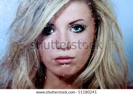 Sad young beautiful woman and a rain drops on the window