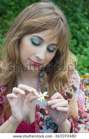 Sad young blond defoliating Daisy in the field