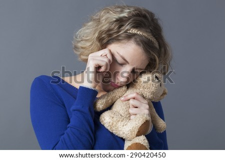 sad young blonde woman hugging her teddy bear with tenderness for emotional reinsurance and child memories - stock photo