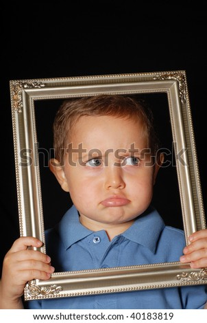 Sad young boy against black background