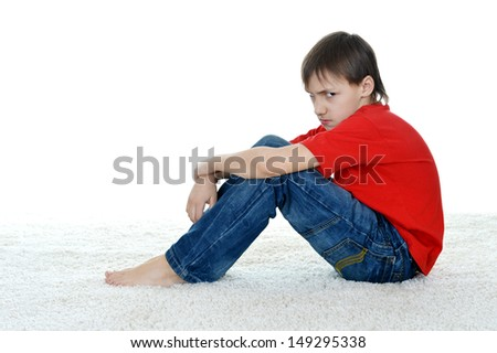 sad young boy in the red shirt on a white background - stock photo