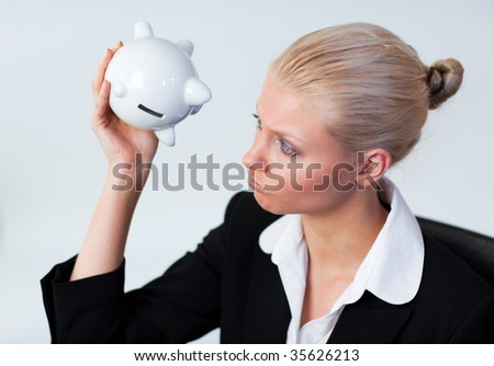 Sad young Business woman looking into Piggy Bank - stock photo