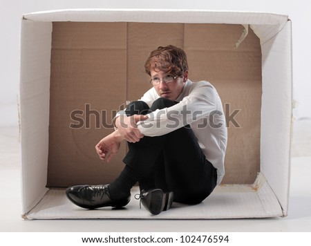 Sad young businessman sitting in a carton - stock photo
