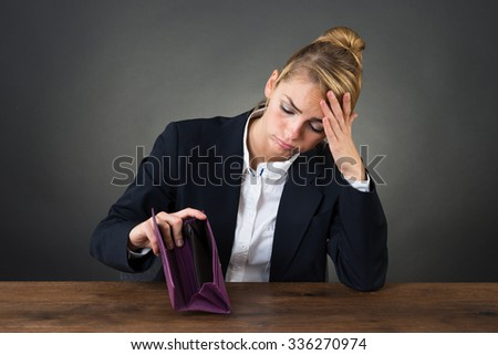 Sad young businesswoman holding empty purse at desk over gray background